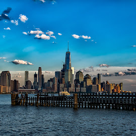 Manhattan Skyline at Dusk by Carol Ward - City,  Street & Park  Skylines ( manhattan skyline, pier a park, manhattan, hoboken, freedom tower, pier clouds, dusk, hudson river )