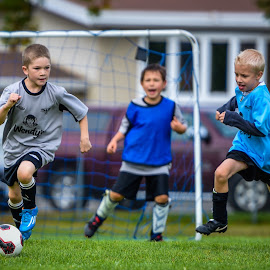 Running with the Ball by Garry Dosa - Sports & Fitness Soccer/Association football ( tournament, ball, blue, outdoors, boys, movement, sports, action, children, grey, game, people, soccer )