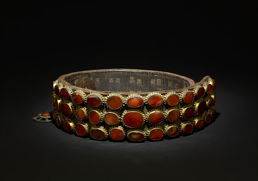 <b>Married woman's belt (Jakičar) from Herzegovina</b> <i>Mid–late 1800s</i>  Formed of a stiff triple layer of leather, this belt is studded with rows of carnelians and agates. At the back are pierced and riveted copper alloy plaques with a clasp at one side. These belts were worn from the wedding onwards.