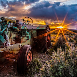 Best Days Behind by Mike Lee - Landscapes Sunsets & Sunrises ( tractors, desert, ruin, antique tractors, rustic, forgotten, sun rays, classic tractors, farm, sun burst, sunset, rust, tractor, decay, abandoned )
