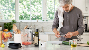 Man using Android phone while cooking in the kitchen