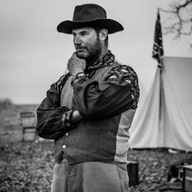 B&W Cowboy in the War by Eva Ryan - People Portraits of Men ( oklahoma, black & white, male, civil war re-enactment, hat, bandana, flag, outdoors, battle of round mountain, tent, campsite, beard, yale_ok, man, vest )