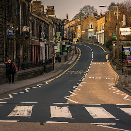 Waiting by Darrell Evans - City,  Street & Park  Street Scenes ( signs, crossing, building, stone, road, road markings, village, outdoor, path, walkway, town, man, wall )