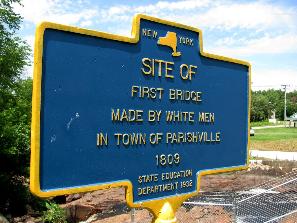 If placed today, I'm sure the wording would be different than what was used in 1932. 'Site of First Bridge Made by White Men in the town of Parishville 1809' The river spanned is the West Branch of ...