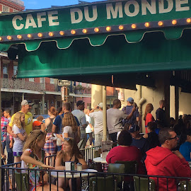 The Original Cafe du Monde in New Orleans by Eric Michaels - Food & Drink Eating ( tables, new orleans, sitting, tourists, chairs, louisiana, eating, cafe du monde, men, restaurant, women, people )
