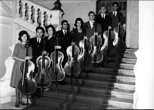 Eight members of Matz's cello class stand with their cellos  around 1960.