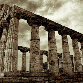 Still strong by Gene Myers - Buildings & Architecture Decaying & Abandoned ( temple, shotsbygene, clouds, building, ancient, greek city, columns, sepia photo, ruins, paestum, italy, gene myers,  )