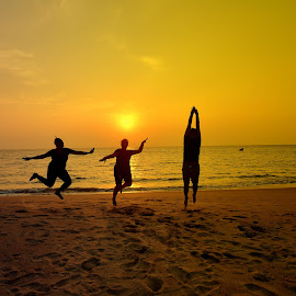 Enjoyment on beach by Manoj Kulkarni - Landscapes Beaches ( water, sand, jumping, enjoying, silhouette, malvan, sea, ocean, quiet, beach, yellow, landscape, jump, sky, vacation, sunset, india, maharashtra, light, evening, black, golden )