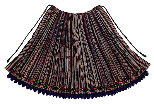 This wool back apron would have been made by women from tough goat or sheep thread. The thread is dyed in several colours and woven in stripes. The apron is then pleated and the pleats tacked in. After baking in a warm oven the tacking is removed and the fabric bound up to retain the pleats. The apron is then sewn onto a waistband and long, thick, plaited tie cords are added.