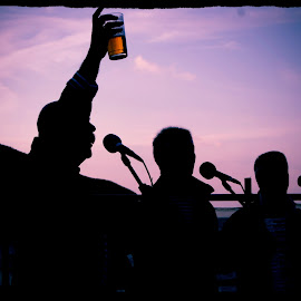 Raising one up ! by Andrew Sledmore - People Musicians & Entertainers ( sky, beer, singing, glass, sea, fun, beach,  )