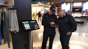 Tikit Kiosk at Bauer (Bloomington, MN) and Bauer staff holding management view on their tablet.