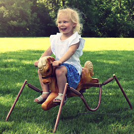 Queenie by Sam Reed - Babies & Children Children Candids ( horse, cutie, bouncey horse, girl, toy, child )