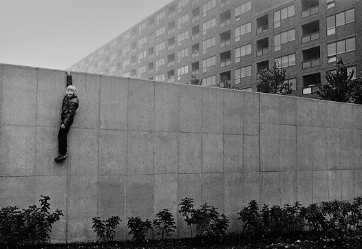 """""""Why don't you take a photo of me hanging on that wall?"""" """"Sure, but how..?"""" """"Just wait and see!"""" says the boy and disappears around the corner. Then he climbs over the edge and shouts: """"NOW!"""" The boy on the wall is Michael Carlsson. He was supposed to participate in a filmed interview about growing up in Hammarkullen in the 1970's, but sadly he passed away at the end of 2016. This exhibition is dedicated to Michael."""
