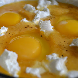 Baked Eggs in Fresh Yellow Tomato Sauce with Mixed Herbs and Goat Cheese