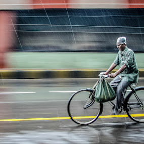 Cycling in The Rain by Dhritiman Lahiri - Transportation Bicycles ( work, iclickweddings best candid photographer in hyderabad, dhritiman lahiri, monsoon, dhritimanlahiri, kolkata, creative wedding photography, cycling, street, hyderabad wedding photographer, street photography, calcutta, best candid photographer in hyderabad, iclickweddings, india, rain )