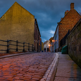 Evening Stroll by Darrell Evans - City,  Street & Park  Street Scenes ( home, old, walking, brick, street, stone, road, people, lights, england, sky, streerlight, buildings, path, walkway, nikon, evening, cobblestone, clouds, building, whitby, dusk, cobbles, railings, blue, d7100, wall )