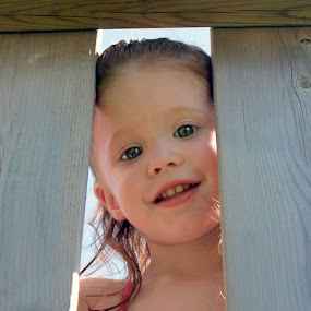 Peeking Through The Boards by Julie Quesnel - Babies & Children Child Portraits ( face, joy, youth, young, kid, eyes, child, fence, girl, happy, pink, green eyes, pwcsummerfun, smile )