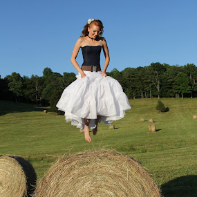 Jumping Bales by Freda Nichols - People Portraits of Women ( field, woman, hay, bales, country,  )