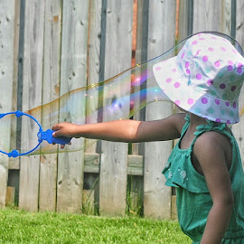 Bubbles by Herb Drummond - Babies & Children Children Candids ( fence, bubble, polka dots, bubbles, sunshine, toddler, green grass )