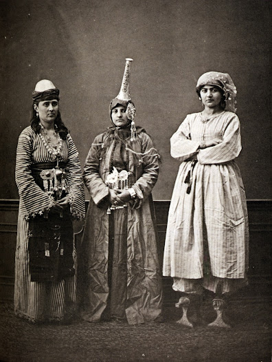Studio portrait of models wearing garments and accessories from Damascus, Syria, during the Ottoman period, 1873. The woman on the right wears stilted <i>qabqab</i>.