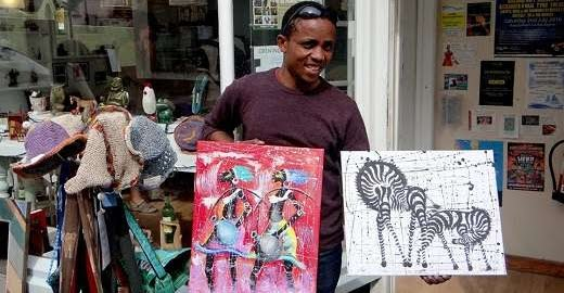 Tanzanian Artist showing his Tinga tinga paintings
