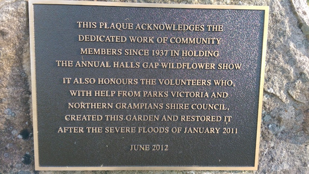 This plaque forms part of a stone sculpture in the Halls Gap Botanic Gardens. Plaque reads: THIS PLAQUE ACKNOWLEDGES THE DEDICATED WORK OF THE COMMUNITY MEMBERS SINCE 1937 IN HOLDING THE ANNUAL HALLS ...