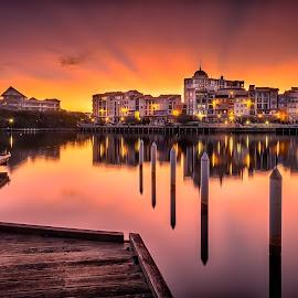 Bursting by Alex Stecina - City,  Street & Park  Vistas ( water, clouds, reflection, warm, lake, architecture, jetty, dusk, rays, colours, sky, sunset, buildings, bridge )