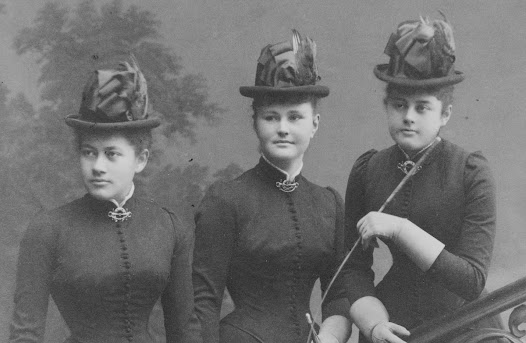 This image is a typical studio photo. Ebba and Ellen, with their cousin Hilma in the middle, are dressed in riding clothes and hats and carry riding crops, in order to give the impression that they are just about to go out for a ride.