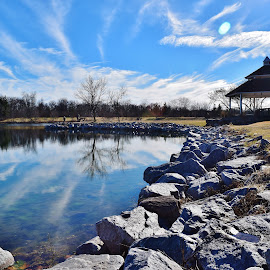 Gazebo in the Spring Afternoon by John Tuttle - Landscapes Weather ( water, clouds, reflection, structure, wood, rock, lake, lens flare, sky, blue, trees, stones, gazebo )