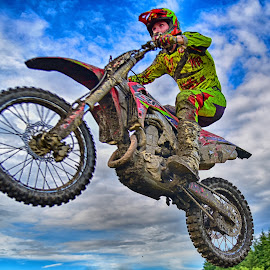 Flying By  by Marco Bertamé - Sports & Fitness Motorsports ( clouds, flying by, speed, green, yellow, race, noise, jump, flying, red, sky, motocross, blue, grey, air, high )