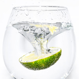 Slice of lime dropping into a glass by Jackie Matthews - Food & Drink Alcohol & Drinks ( fruit, citrus, drink, glass, white background, lime, slice of lime, fizz )