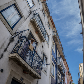 Curious one by Julija Moroza Broberg - City,  Street & Park  Street Scenes ( urban exploration, person, urban landscapes, street art, old town, architecture, street scene, lisbon, lookup, urban sky, ancient, curious, city view, perspective, portugal, balcony, narrow street, city scene, city life, architectural detail, street photography, urban, old lady, summer, view, lisboa, daylight )