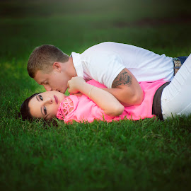 Stealing a kiss by Carole Brown - People Couples ( brown eyes, pink shirt, white shirt, brown hair, laying in grass )