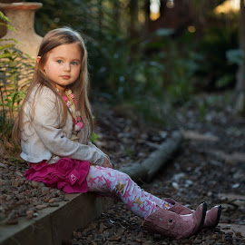 The Fading Afternoon Glow by Belle Farley - Babies & Children Child Portraits ( long hair, beautiful, sunlight, stone path, portrait, cowgirl boots, child, sitting, girl, afternoon glow, sunset, garden, golden hour )