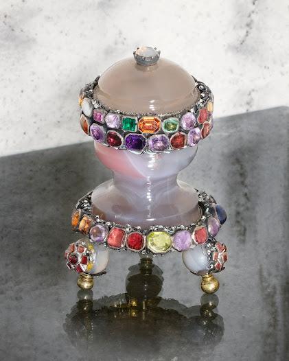 Prydnadsföremål av agat med montering i förgyllt silver med emalj. Stenarna är bl.a. vit opal, granat, ametist, smaragd, hessonitgranat, olivin (peridot), bergkristall, zirkon och safir.