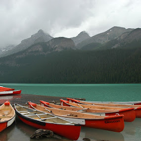Stormy Day at Lake Louise  by Deb DeKoff - Landscapes Waterscapes ( lake louise, stormy, mountains, red boats, canada, lake, dreary, canoes, rain )