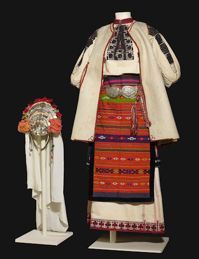 <b>Wedding costume and headdress (kaitsa)</b> Pleven, North Bulgaria Early 1900s  This festive costume for a married woman is designed to be practical – for working in the fields in the grain growing areas of the Danubian plain in northern Bulgaria.    It is a 'two-apron' costume. Instead of the customary fitted over-garments, the long linen chemise or shift was covered by aprons at the front and back, and a loose sleeveless coat. The chemise hem has a row of dancing women as symbols of fertility.
