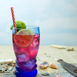 Tropical Drink  by Jim Downey - Food & Drink Alcohol & Drinks ( chilled, sand, shells, blue glass, straw, raspberry, ice, gin, lime, beach, lemon )