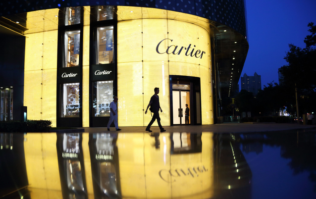 A pedestrian walks past a Cartier store, operated by Richemont, as it stands illuminated at night in Shanghai, China. Picture: BLOOMBERG