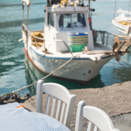 Typical greek restaurant and boat by Deyan Georgiev - Food & Drink Eating ( interior, shop, old, europe, mykonos, chairs, street, travel, house, architecture, beach, crete, restaurant, island, typical, mediterranean, resort, flowers, santorini, classic, building, greek, coffee, greece, white, sea, tourism, tavern, traditional, table, tables, chair, blue, food, outdoor, taverna, cafe, islands, summer )
