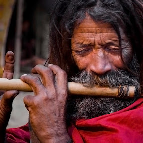 A sadhu playing flute by Saumalya Ghosh - People Street & Candids