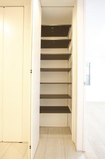 1階:廊下収納の棚は可動式のため、スティック掃除機等も収納可。
