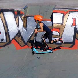 A boy on a scooter by Svetlana Saenkova - Sports & Fitness Cycling ( orange, scooter, boy, orange helmut, grey )