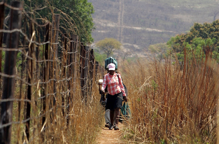 People walk along the fence marking the SA's border with Mozambique. Picture: SOWETAN