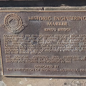 Plaque reads: 'HISTORIC ENGINEERING MARKER. KINGS BRIDGE COMPLETED IN 1864 THIS BEAUTIFUL. WROUGHT IRON ARCH BRIDGE WITH A SPAN OF 60 METRES, WAS DESIGNED BYENGINEER WILLIAM THOMAS DOYNE. IT WAS ...
