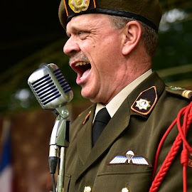 Entertaining Sgt Wilson by Marco Bertamé - People Musicians & Entertainers ( army, open mouth, red, microphone, signing, metal, uniform, green, cap, entertainment )
