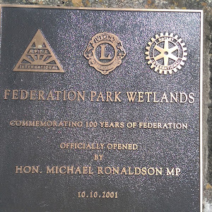 Plaque on the outskirts of Stawell at the start of a short boardwalk.  Has the Apex club, Lions club and Rotary club logos on the top. Plaque reads: Federation Parks Wetlands Commemorating 100 years ...