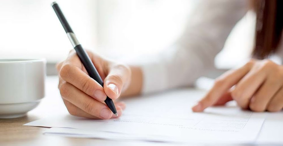 a woman signing a document with a black pen