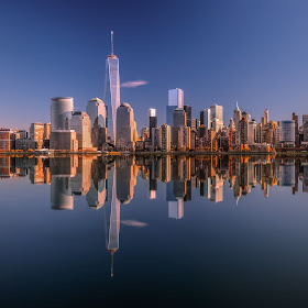 Lower Manhattan skyline panorama over East River with reflection at sunset 2.jpg