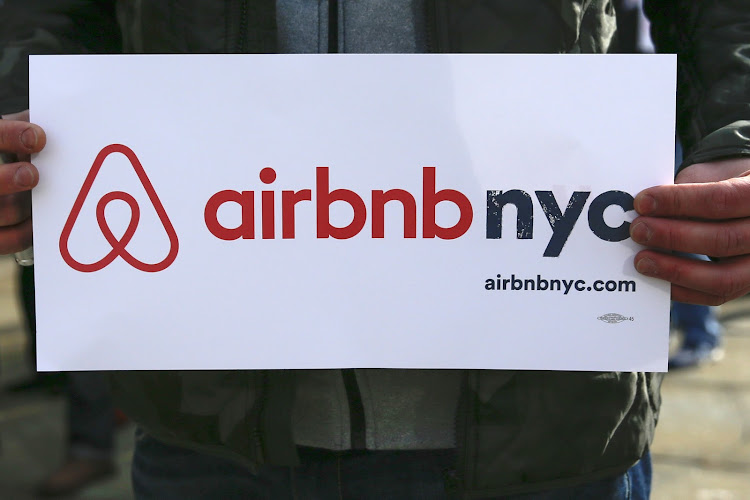 An Airbnb supporter holds a sign during a rally at City Hall in New York.